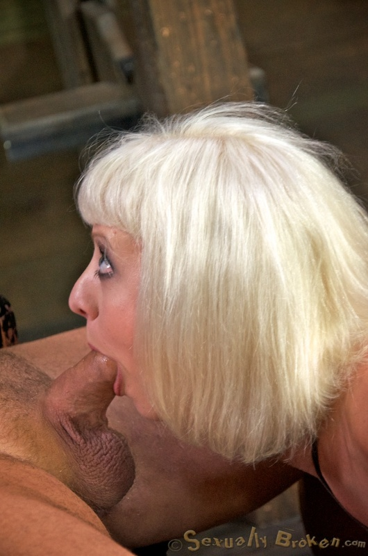 Gagged blonde submissively sucks a massive boner